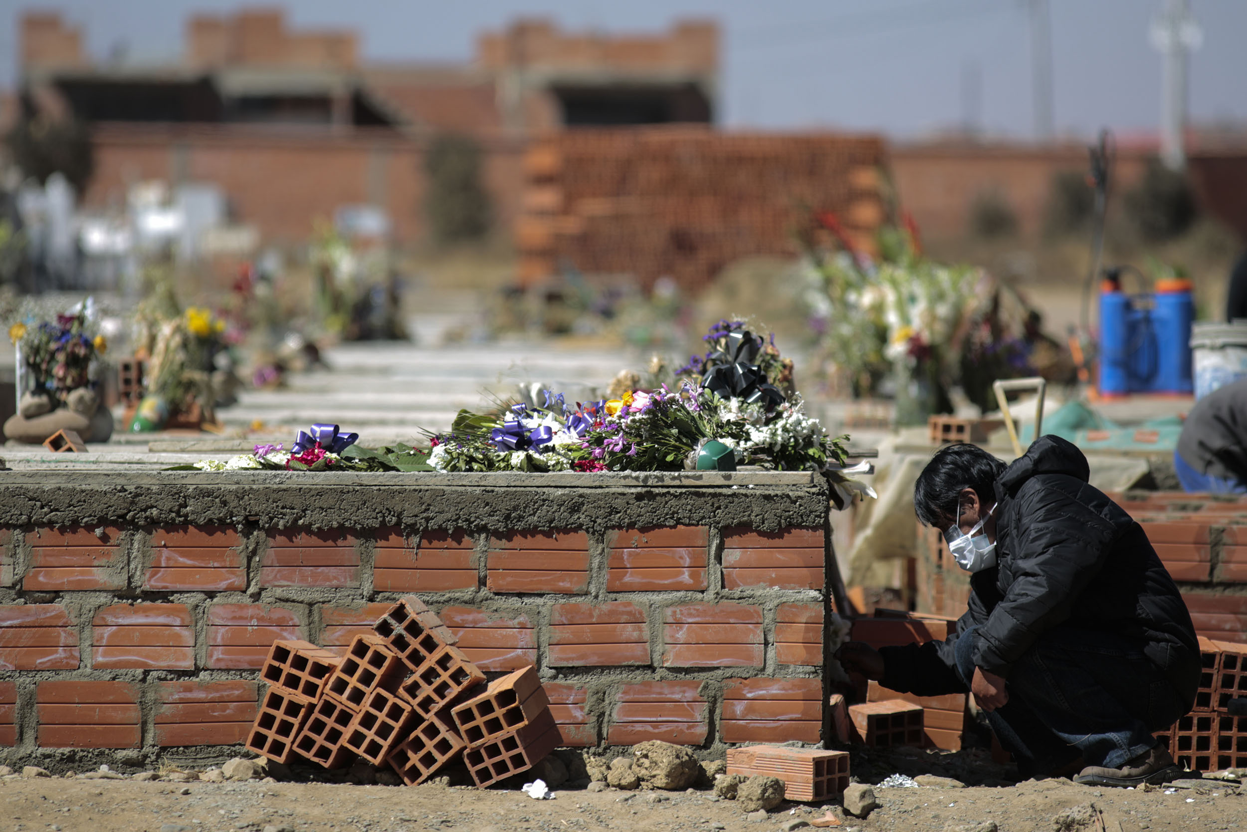 A mourner writes the names of the deceased on the fresh cement at Mercedario Cemetery on July 29, in El Alto, Bolivia.