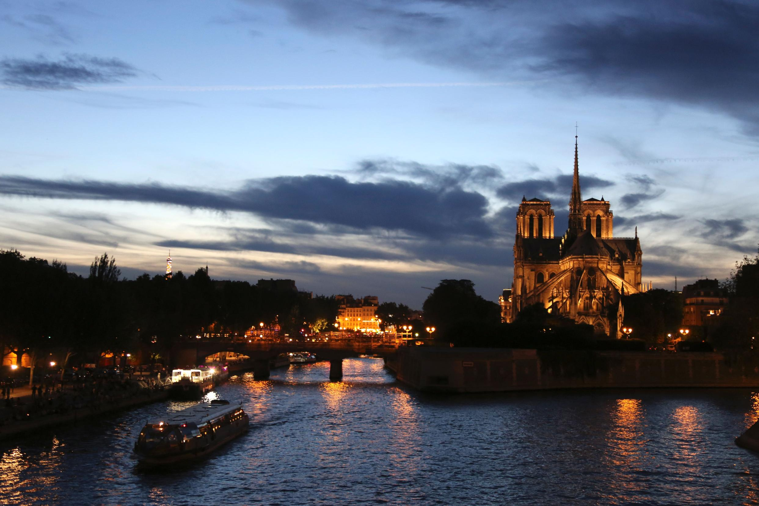 This picture taken in 2016 shows tourist boats cruising on the Seine river alongside the cathedral at sunset.