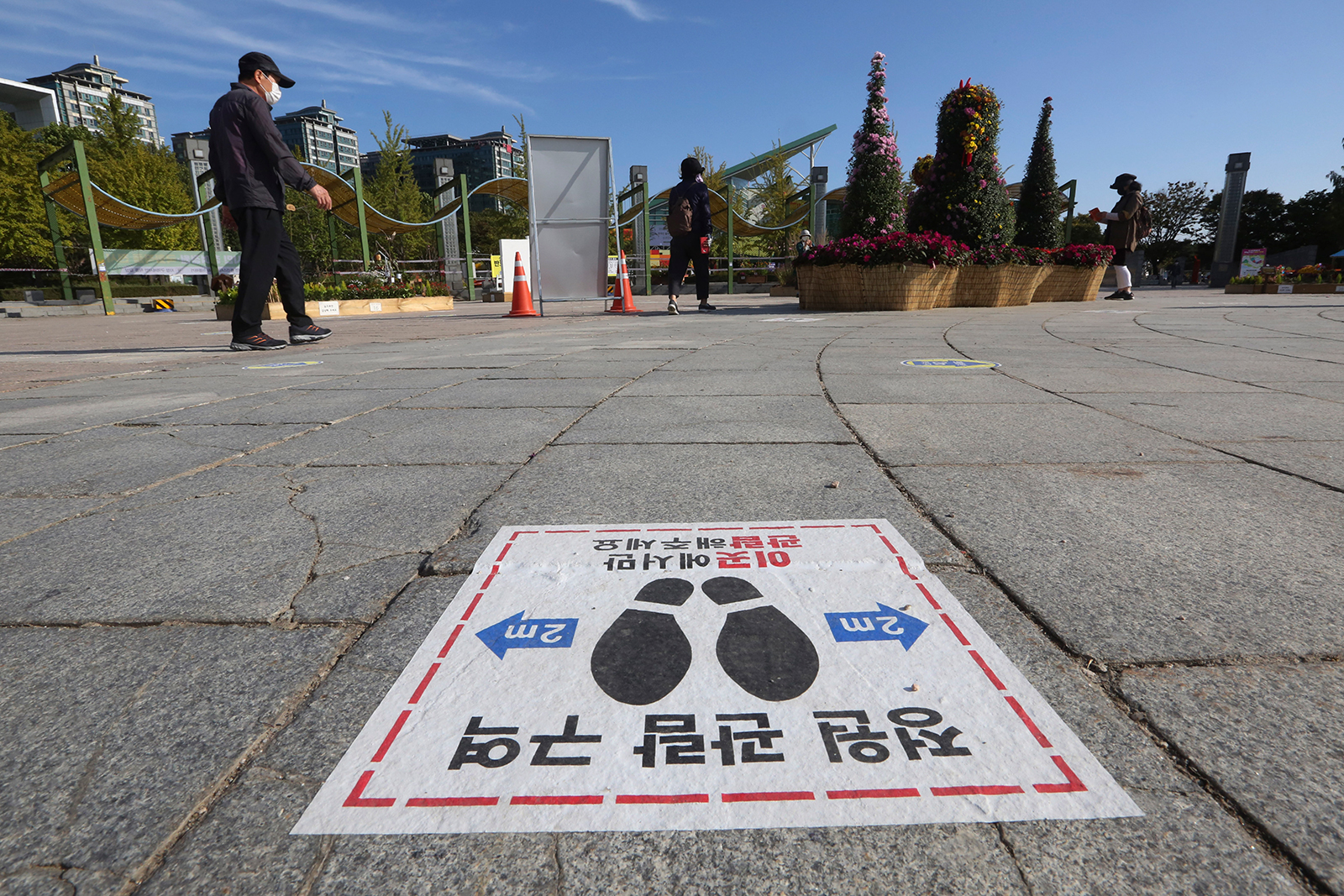 "A social distancing sign is seen on the ground to help curb the spread of the coronavirus at a park in Goyang, South Korea, on October 6. The signs read: ""Please watch here."""