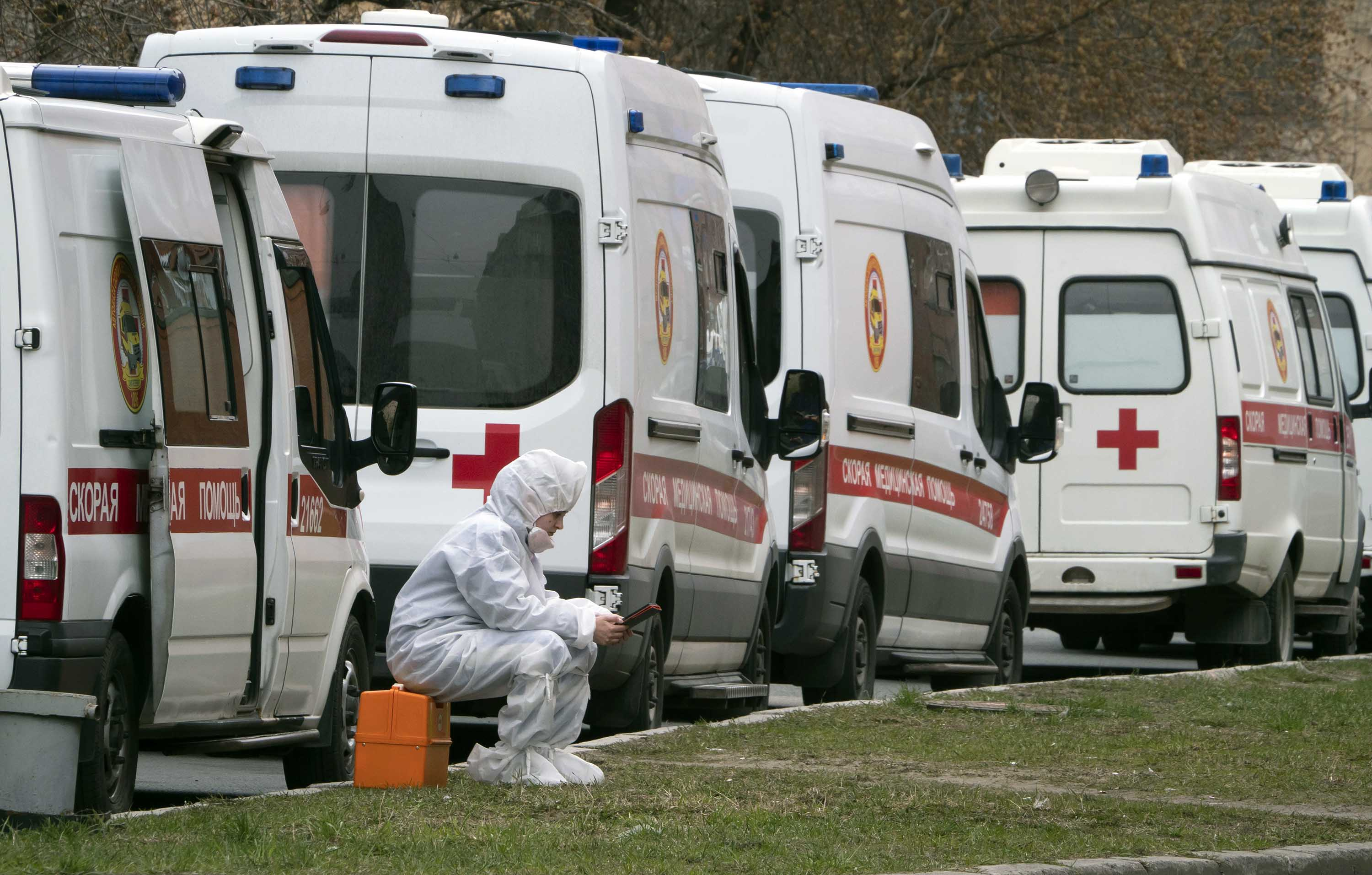 A medical worker waits near a line of ambulances queued to deliver patients suspected of being infected with the coronavirus to the Pokrovskaya hospital in St.Petersburg, Russia, on April 28.
