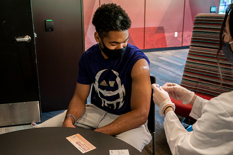 Julius Irvin, a student athlete on the football team, receives a COVID-19 vaccine at a vaccination clinic on the University of Washington campus on May 18, in Seattle, Washington.