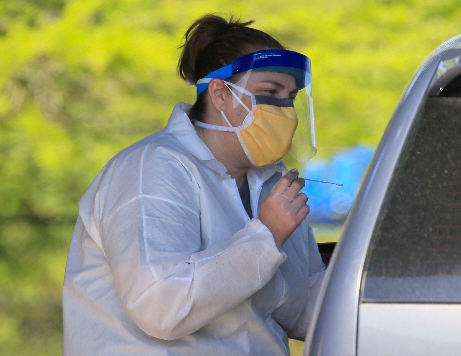 Nurse Tonya Green administers a coronvirus test at a drive-thru testing center in North Little Rock, Arkansas, on April 20.
