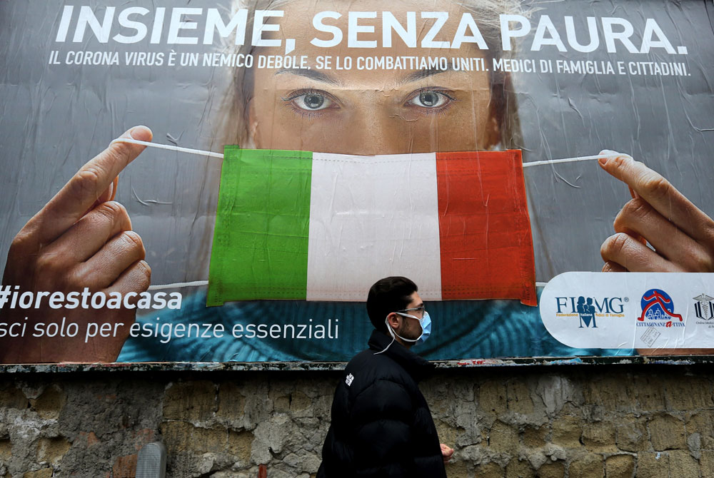 A man walks past a billboard raising awareness to the coronavirus measuresimplemented by the Italian government in Naples on March 22.