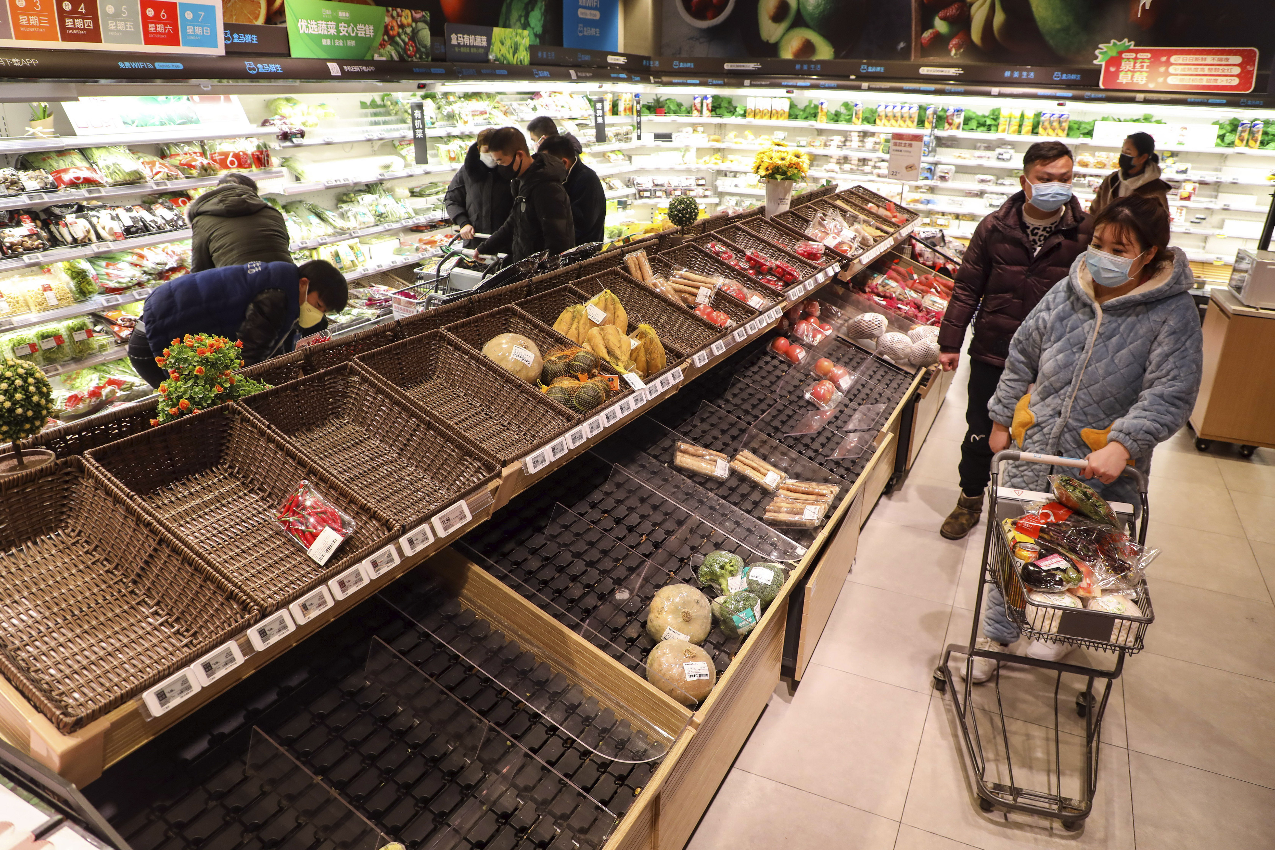 Shoppers wearing face masks look for groceries with many empty shelves at a supermarket in Wuhan on Saturday.