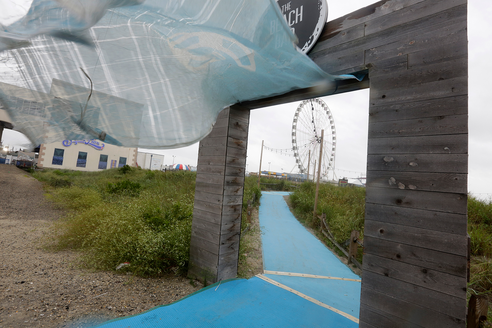 A tarp meant to close a seaside restaurant is blown by wind Tuesday, Aug. 4, in Atlantic City, New Jersey.