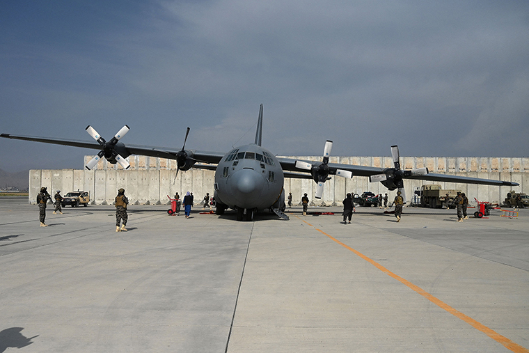 Taliban fighters stand guard next to an Afghan Air Force aircraft at the airport in Kabul on August 31, following the US withdrawal from Afghanistan.