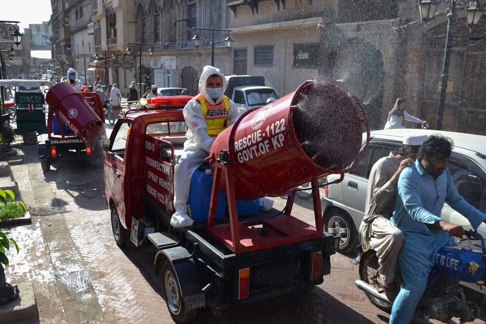 Rescue workers spray disinfectant along a road during a government-imposed nationwide lockdown as a preventative measure against the spread of the coornavirus in Peshawar on May 6.
