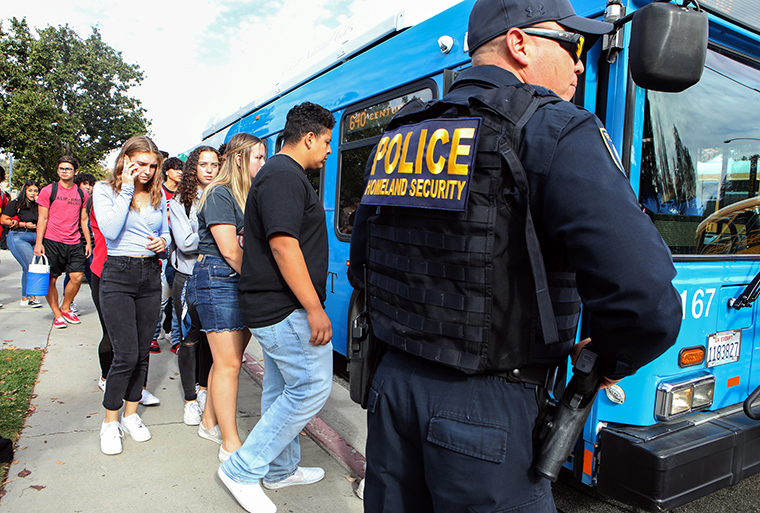Students are evacuated from Saugus High School onto a bus after a shooting at the school left two students dead and three wounded.
