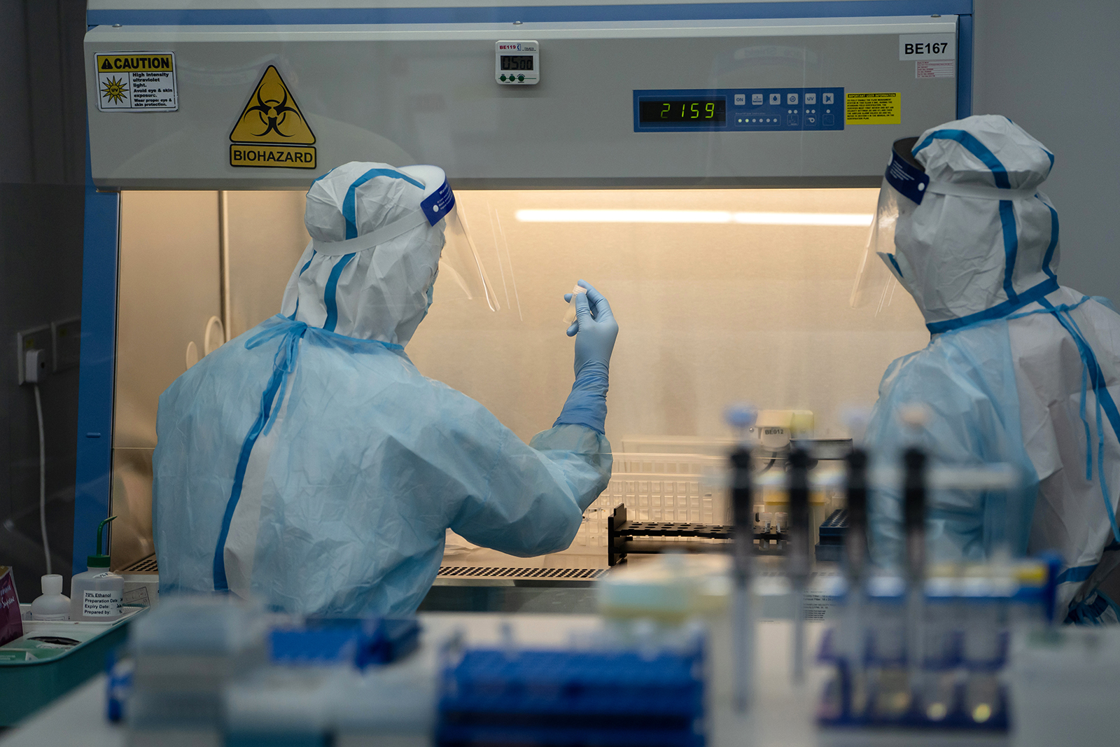 A lab technician wearing a protective suit holds up a saliva sample for RT-PCR Covid-19 testing at Prenetics Ltd.'s laboratory in Hong Kong, China on July 31.