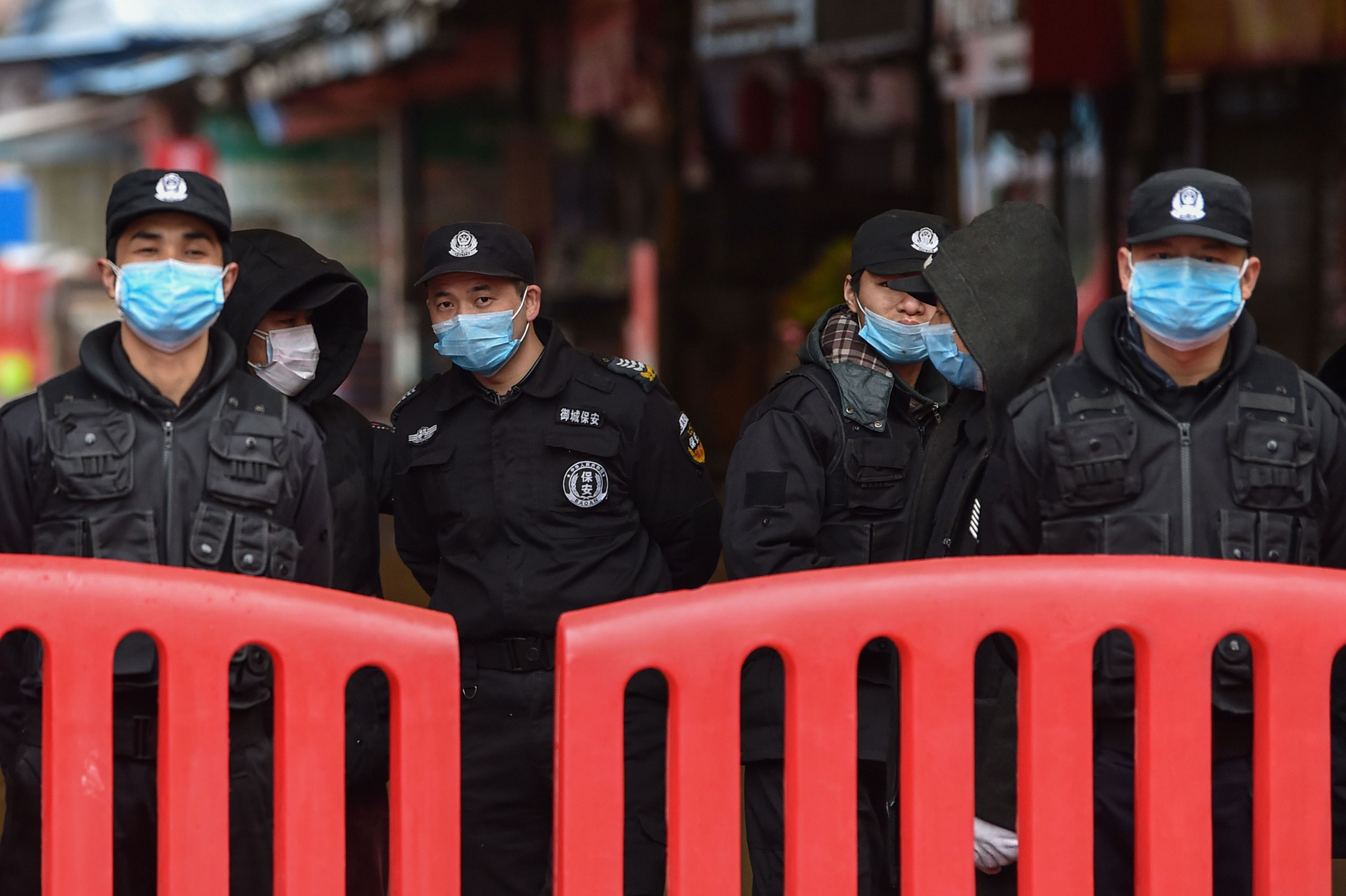 Authorities stand outside the Huanan Seafood Wholesale Market where the coronavirus was detected in Wuhan on January 24.