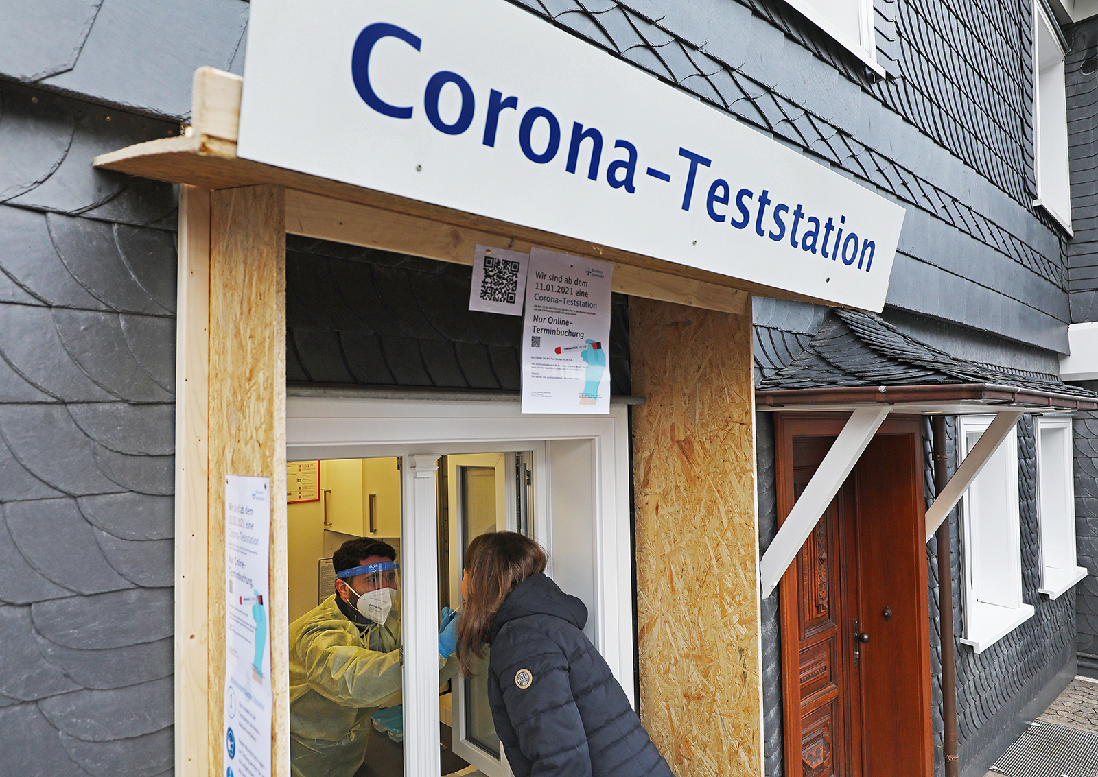 A pharmacist takes a swab from a woman at a coronavirus testing station at the Brunnen pharmacy in North Rhine-Westphalia, Wipperfürth, Germany, on January 14.
