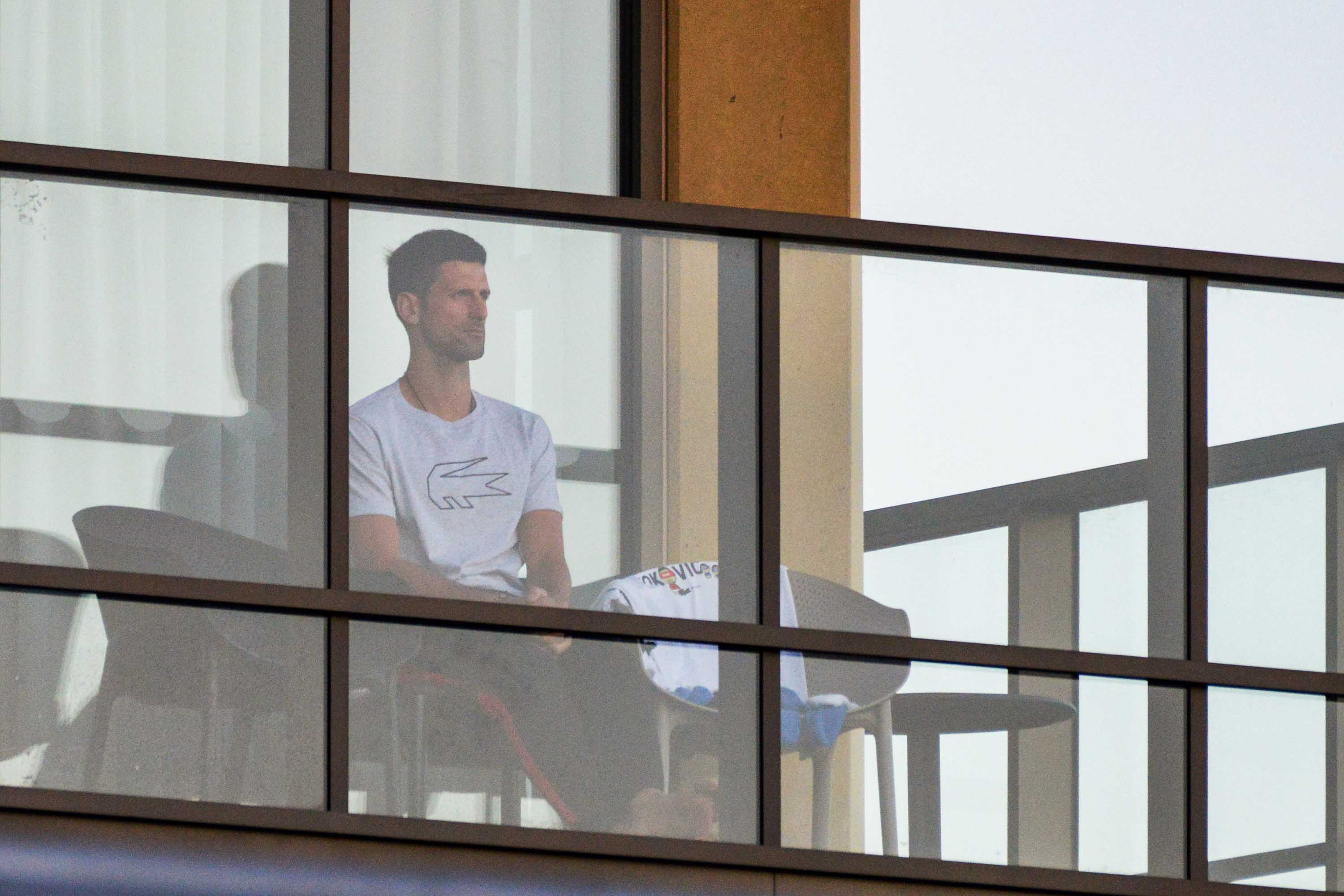 Novak Djokovic sits on his hotel balcony on January 18 in Adelaide, Australia, where players have quarantined for two weeks upon their arrival ahead of the Australian Open tournament in Melbourne.