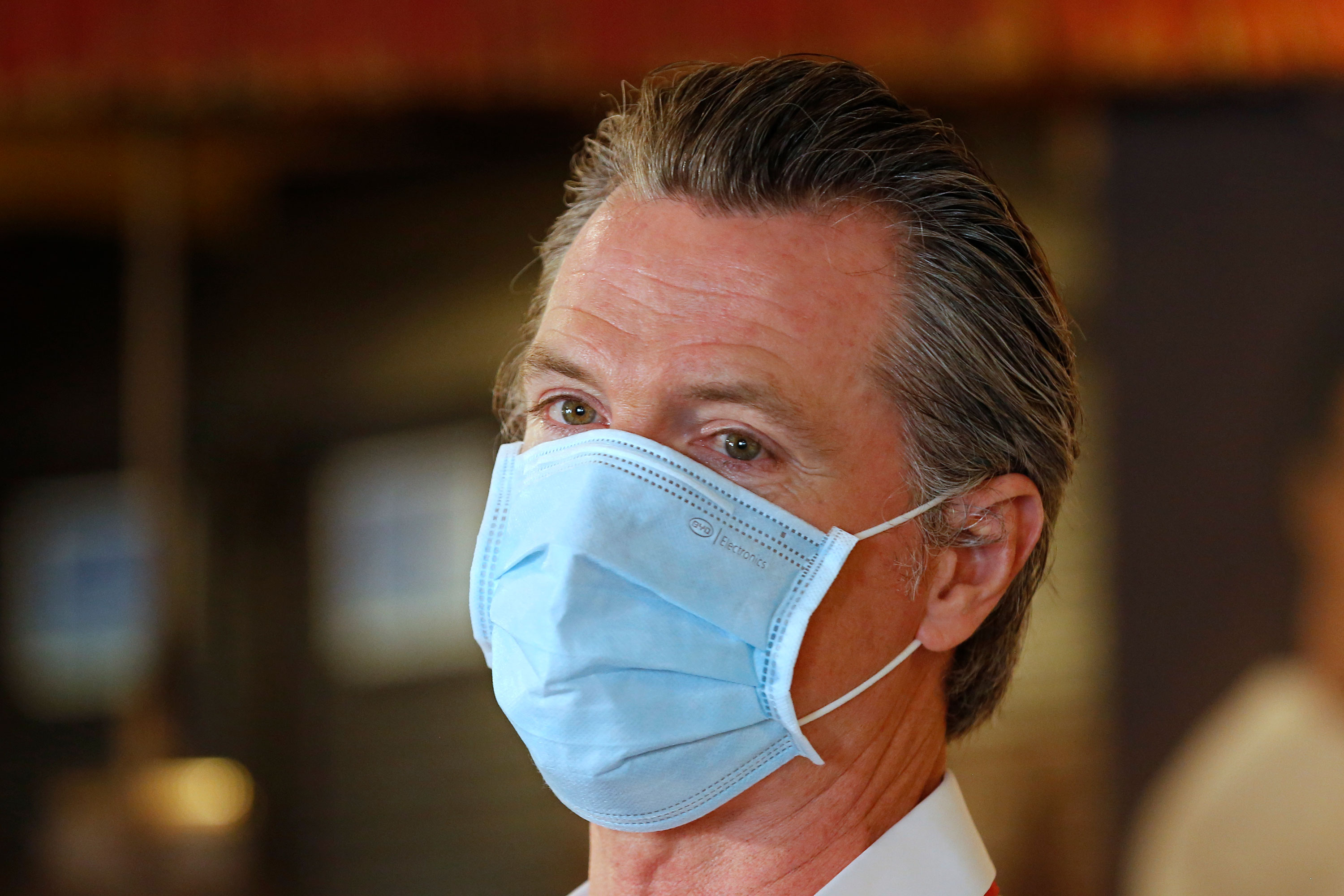 Gov. Gavin Newsom, wears a face mask during his visit to the Queen Sheba Ethiopian Cuisine restaurant on June 19 in Sacramento, California.