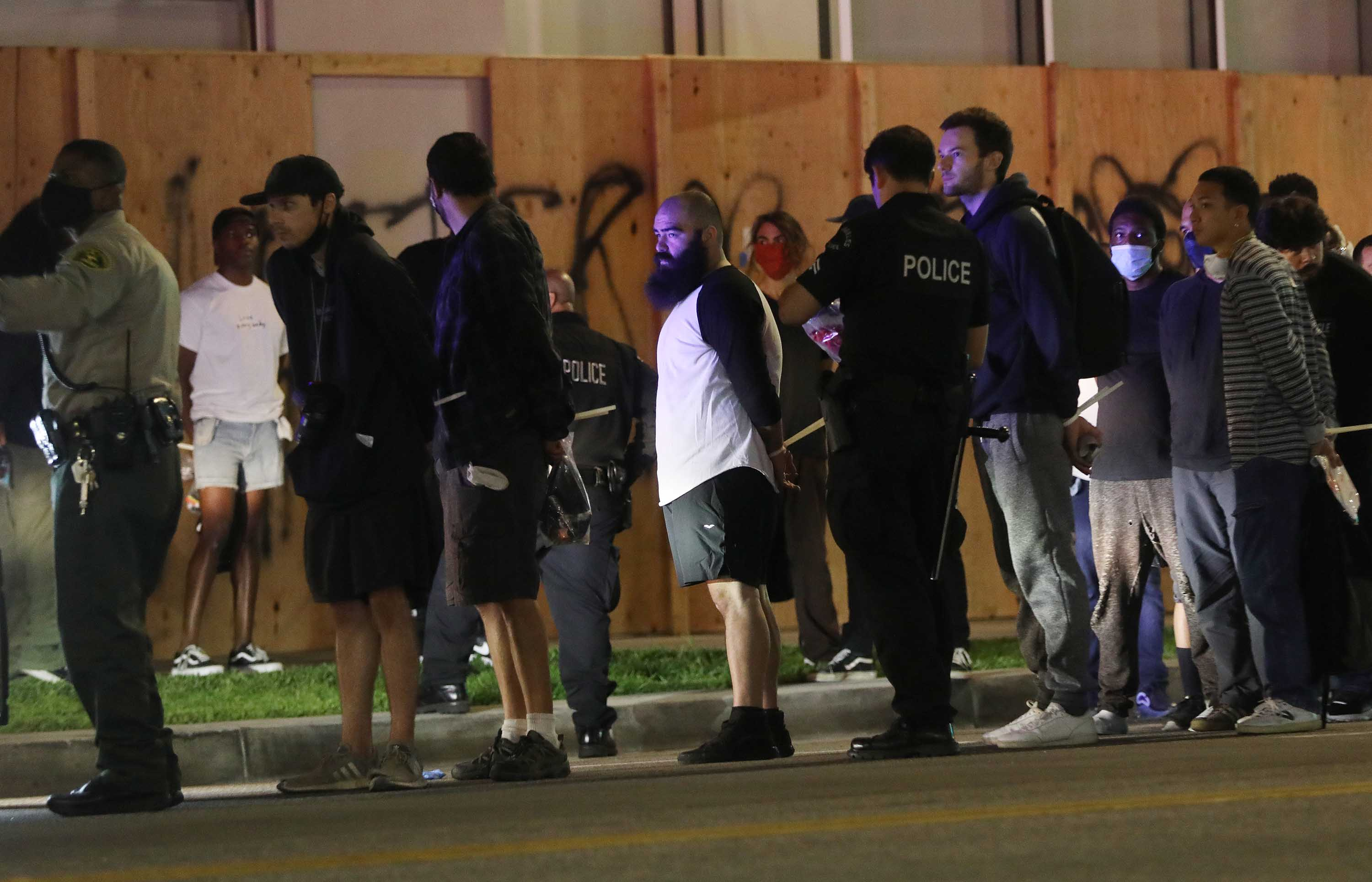 People stand handcuffed by police in the Hollywood area during an emergency curfew on June 1 in Los Angeles, California.