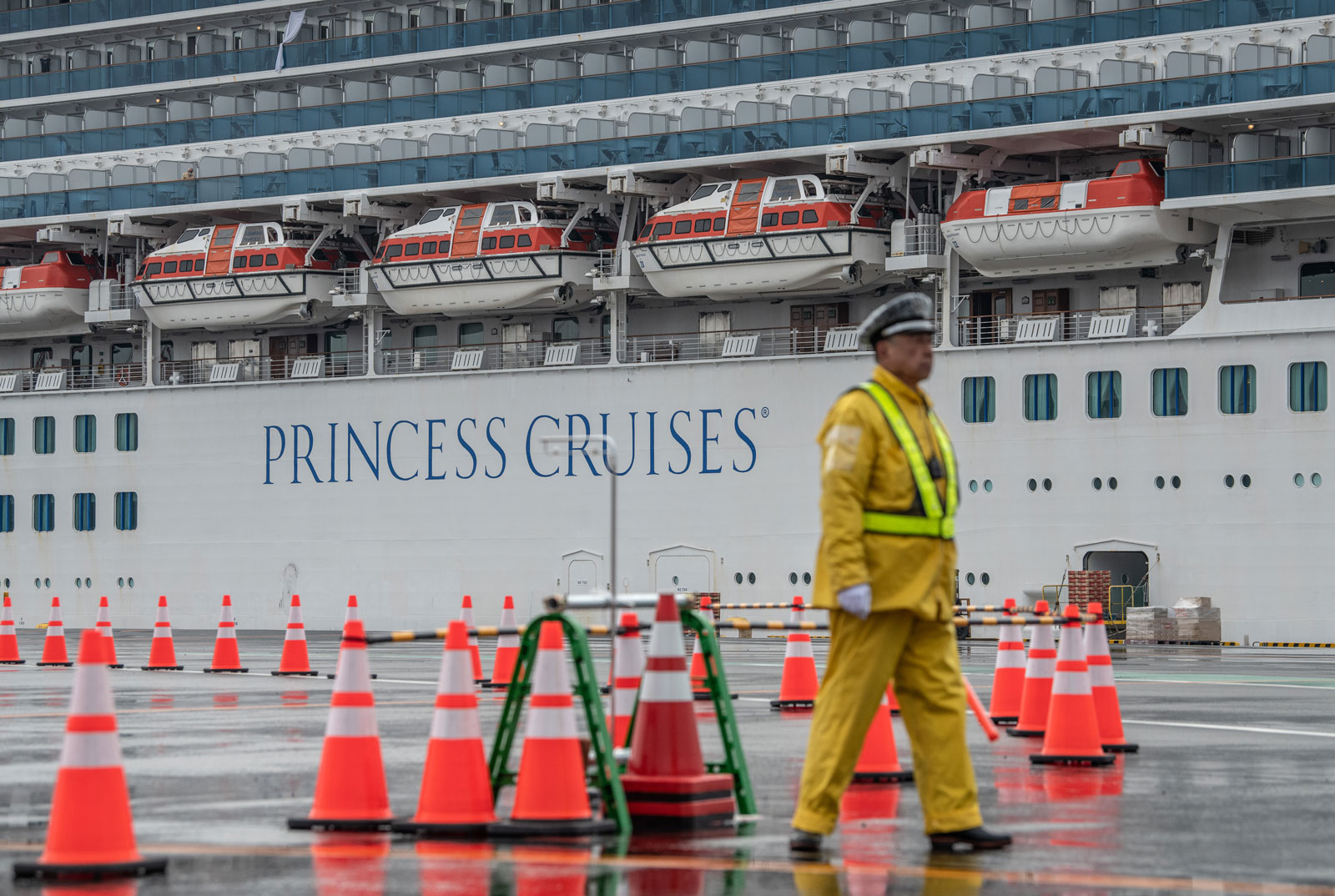 A security guard mans an entrance to Daikoku Pier, where the Diamond Princess cruise ship is being resupplied and newly diagnosed coronavirus cases taken for treatment on February 13 in Yokohama, Japan.