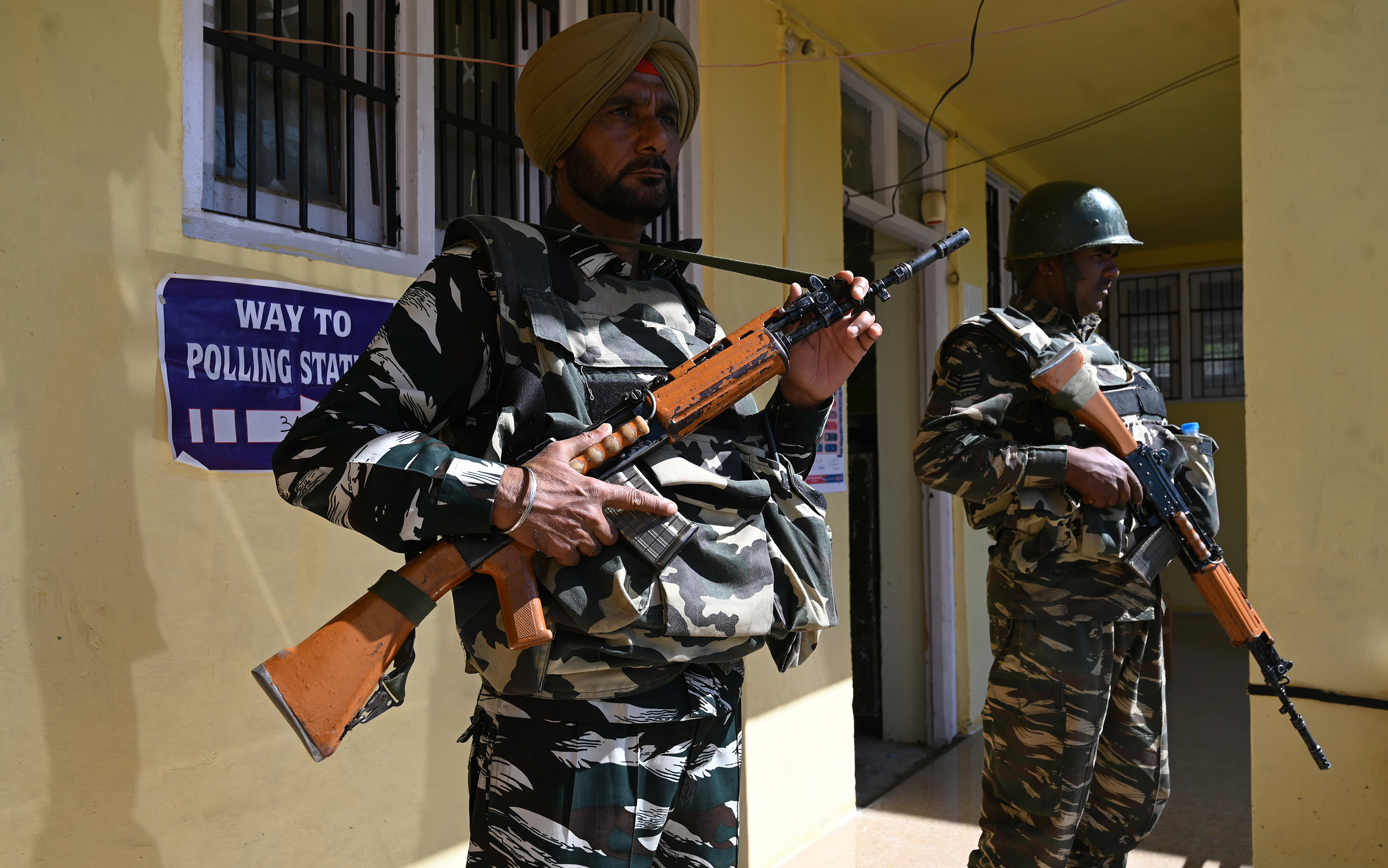Indian paramilitary troopers stand guard at a polling station in Shopian district in Jammu and Kashmir on May 6, 2019.