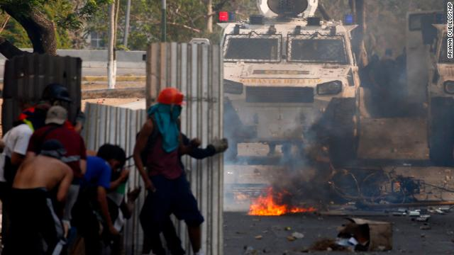 Protesters stand off with guards in Caracas Tuesday.