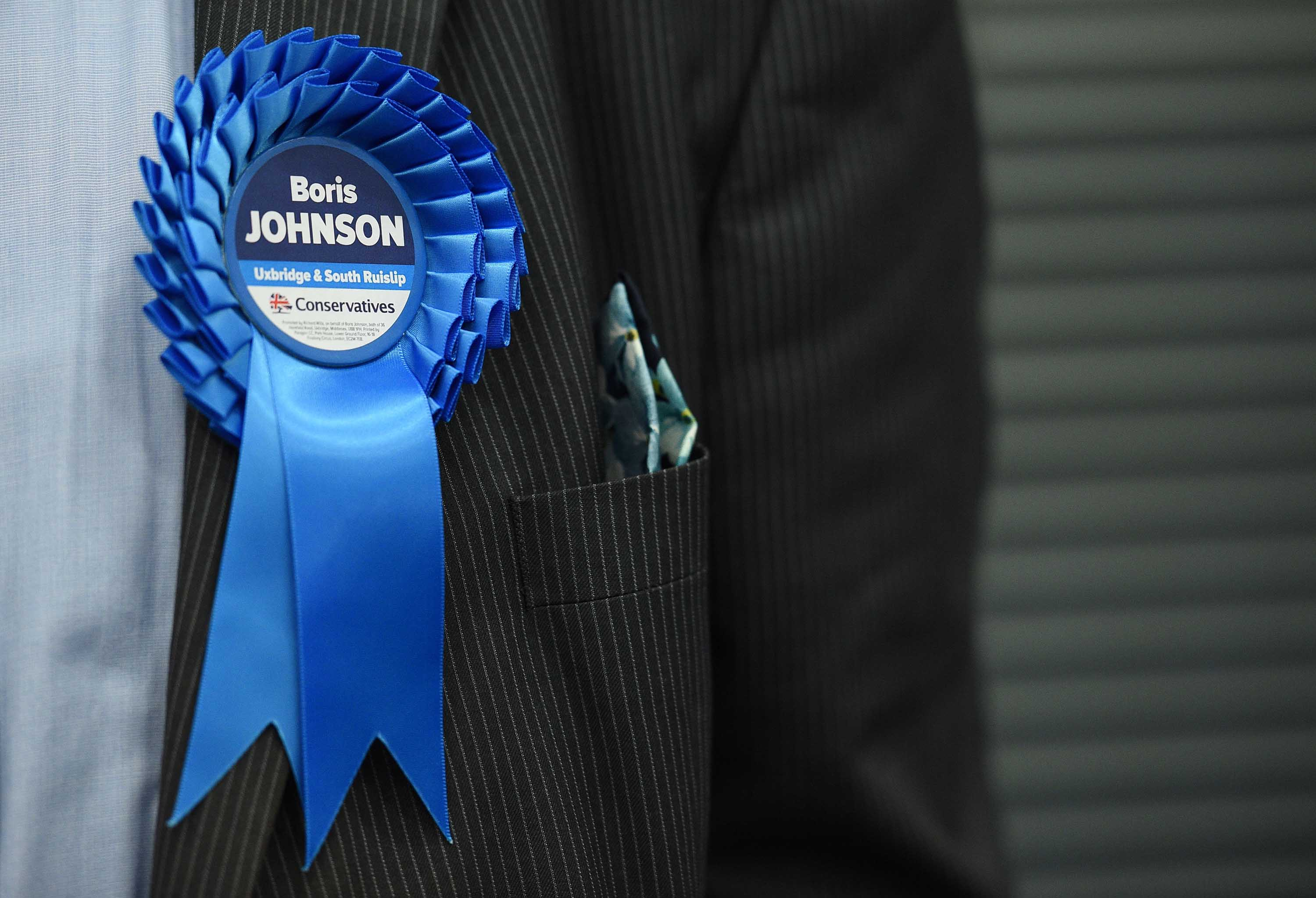A Conservative Party activist wears a rosette as ballots are tallied in Uxbridge, England. Photo: Oli Scarff/AFP via Getty Images