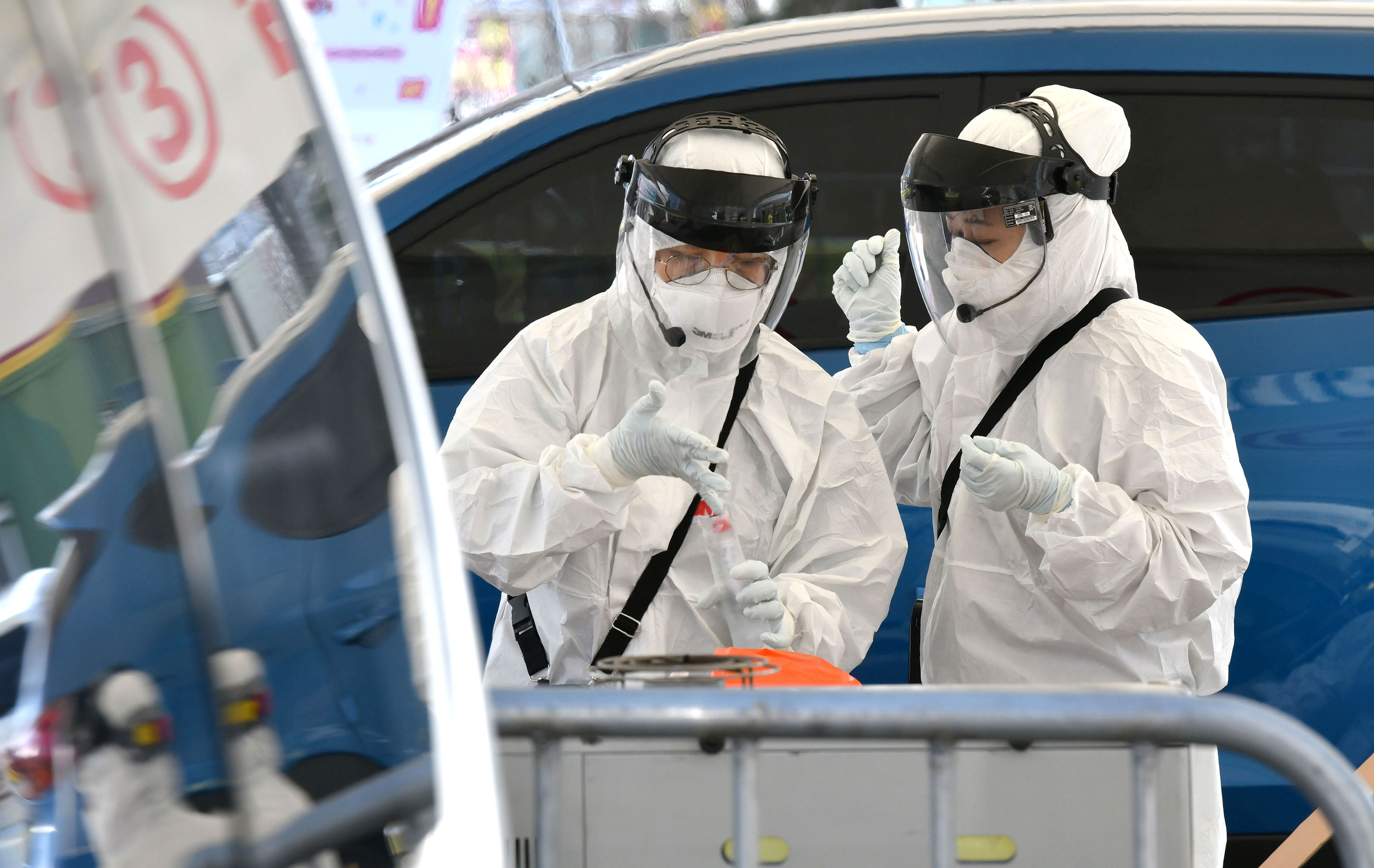 "Medical workers take samples at a ""drive-through"" coronavirus test facility in Goyang, South Korea on February 29."