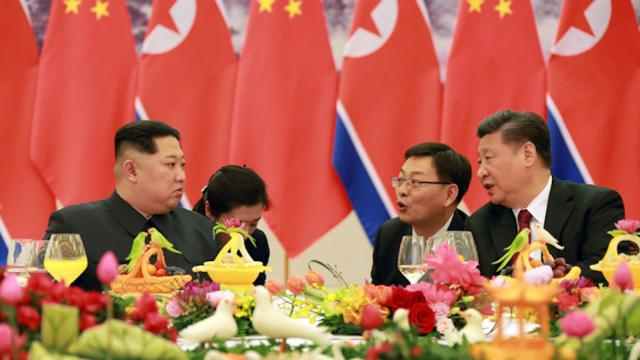 Kim Jong Un, left, and Xi Jinping, right, are seen at a banquet in this photo released by North Korean state media from the two leaders' first meeting in March 2018.