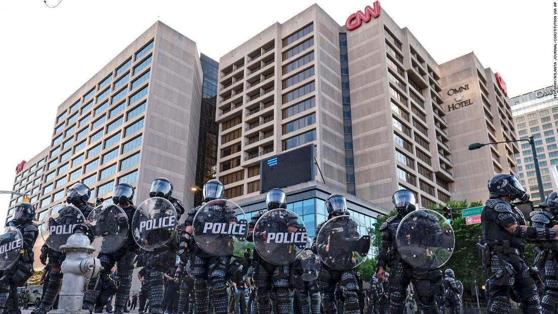 Police stand guard around the CNN Center and Centennial Olympic park as protests continue over the death of George Floyd, on Saturday, May 30, in Atlanta.