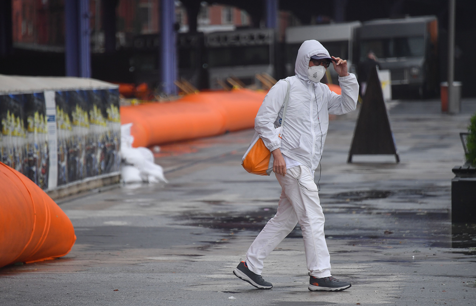 A person walks past flood barriers in lower Manhattan as Tropical Storm Isaias approaches New York City on August 4.