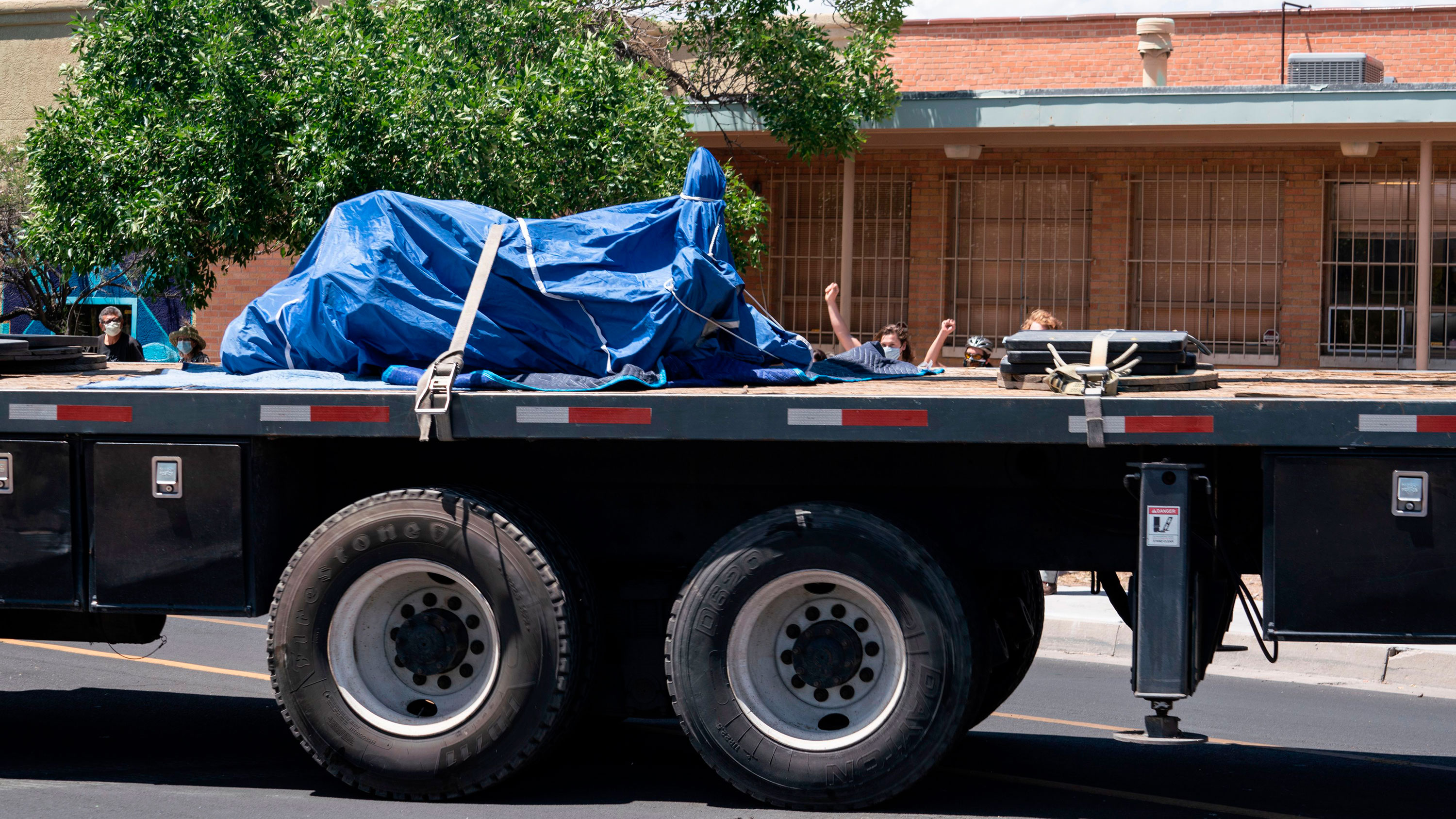 People raise their fists as the statue of Juan de Oñate is hauled away from the grounds of the Albuquerque Museum in Albuquerque, New Mexico, on June 16.