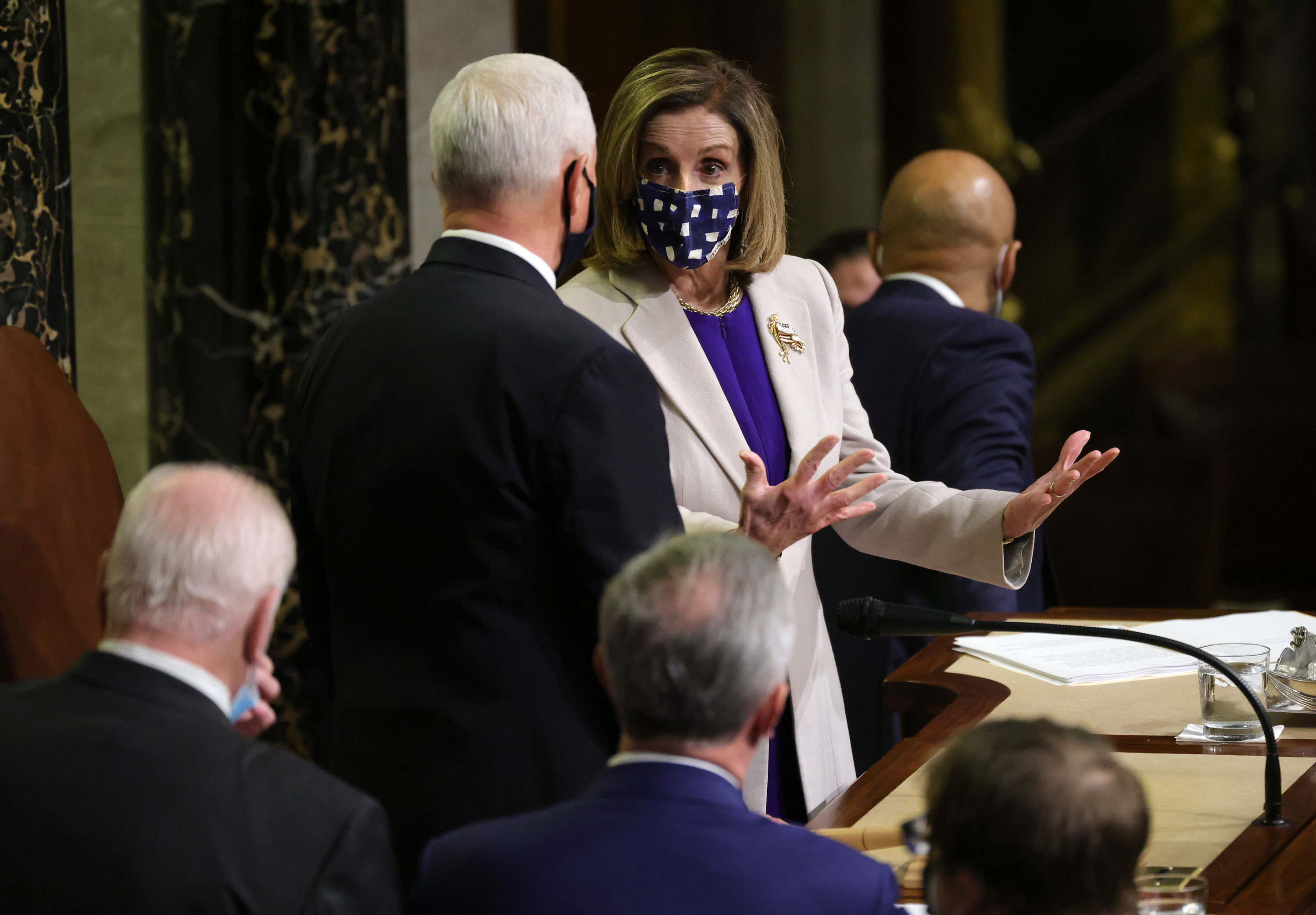 Speaker of the House Nancy Pelosi talks with Vice President Mike Pence after the conclusion of the count of electoral votes in the House Chamber on January 7.