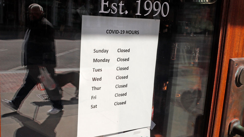 """A sign on the front door of a culinary store lists their """"Covid-19"""" business hours, with every day shown as closed, in Concord, New Hampshire on Monday, April 20."""