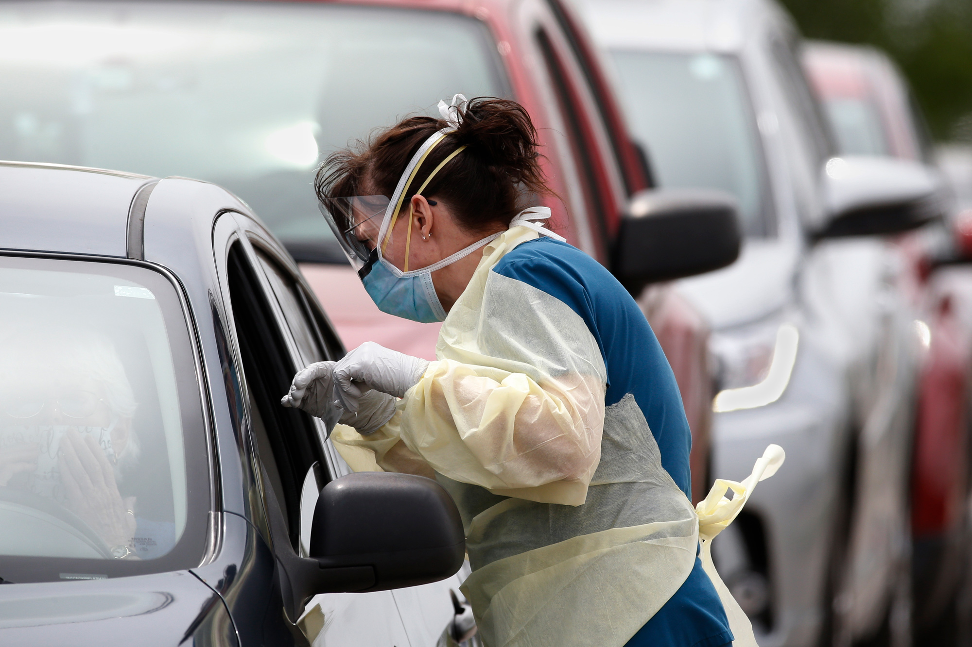 A Cleveland County Health Department employee speaks to a driver of a car at a mobile testing site for COVID-19 in Norman, Oklahoma on April 9.