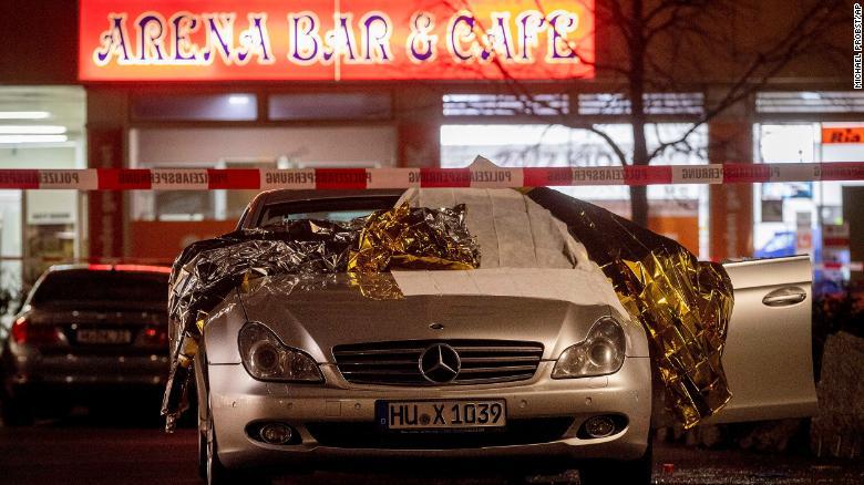 Forensic experts work around a damaged car after a shooting in Hanau near Frankfurt, Germany, February 20, 2020.