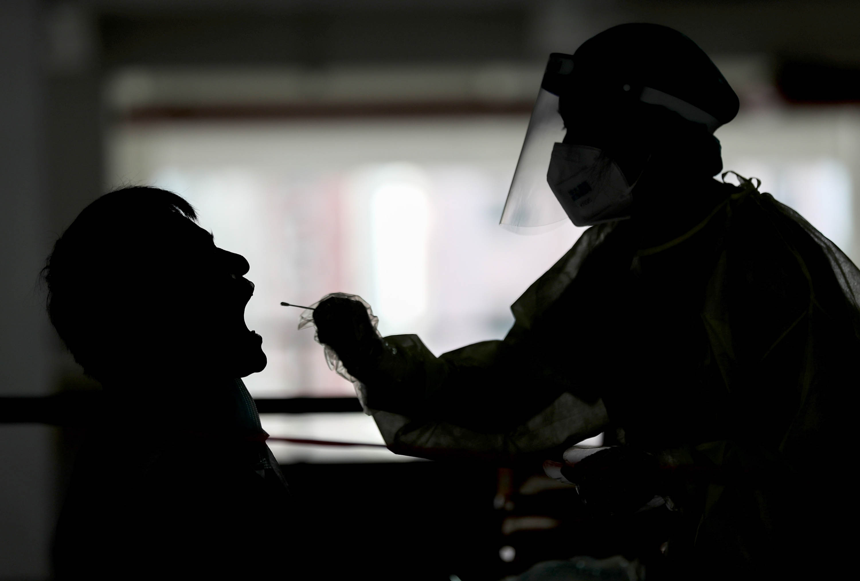 A health worker takes a swab from a taxi driver at a makeshift testing station in a Hong Kong carpark on July 20.