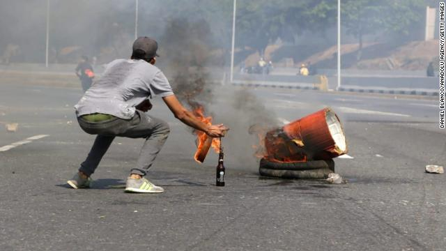 A pro-coup supporter throws a molotov cocktail near military base of La Carlota, in Caracas, Venezuela.