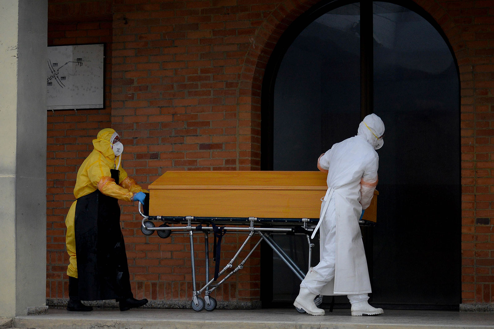 Funeral workers prepare to cremate a coronavirus victim at Serafin cemetary near Bogota, Colombia, on July 4.