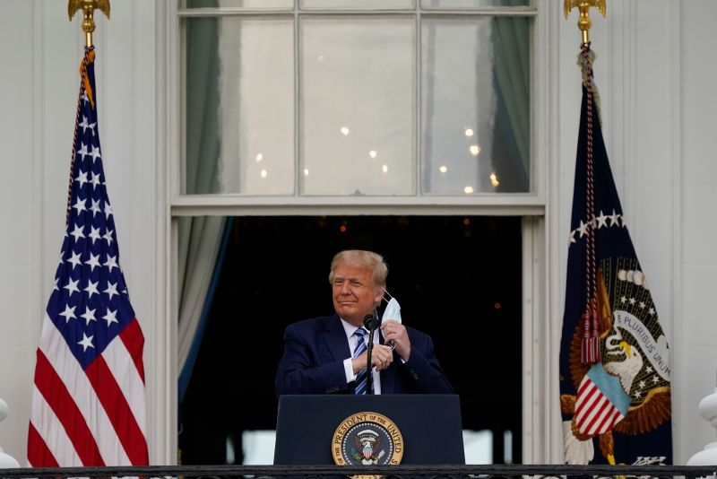 President Donald Trump removes his face mask before speaking to supporters at the White House on October 10.