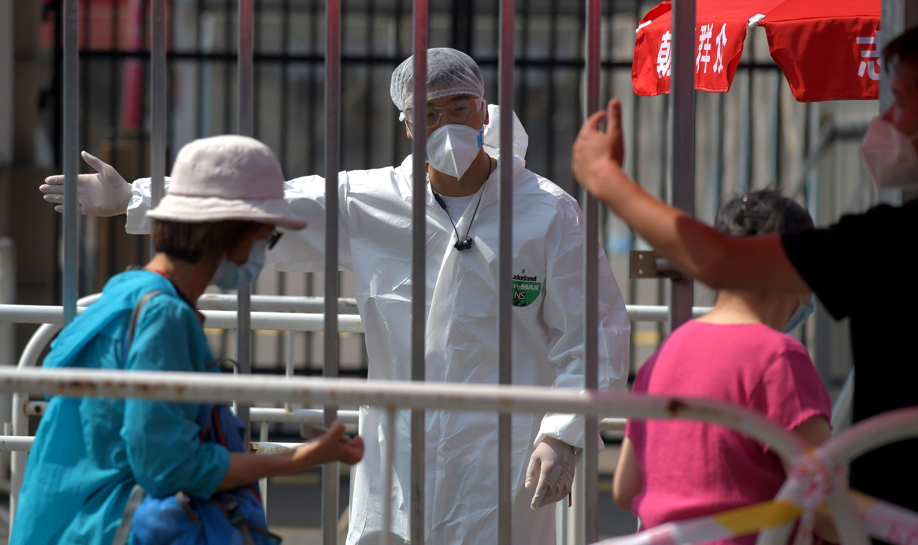 Workers direct people at a coronavirus testing station on June 30 in Beijing, China.