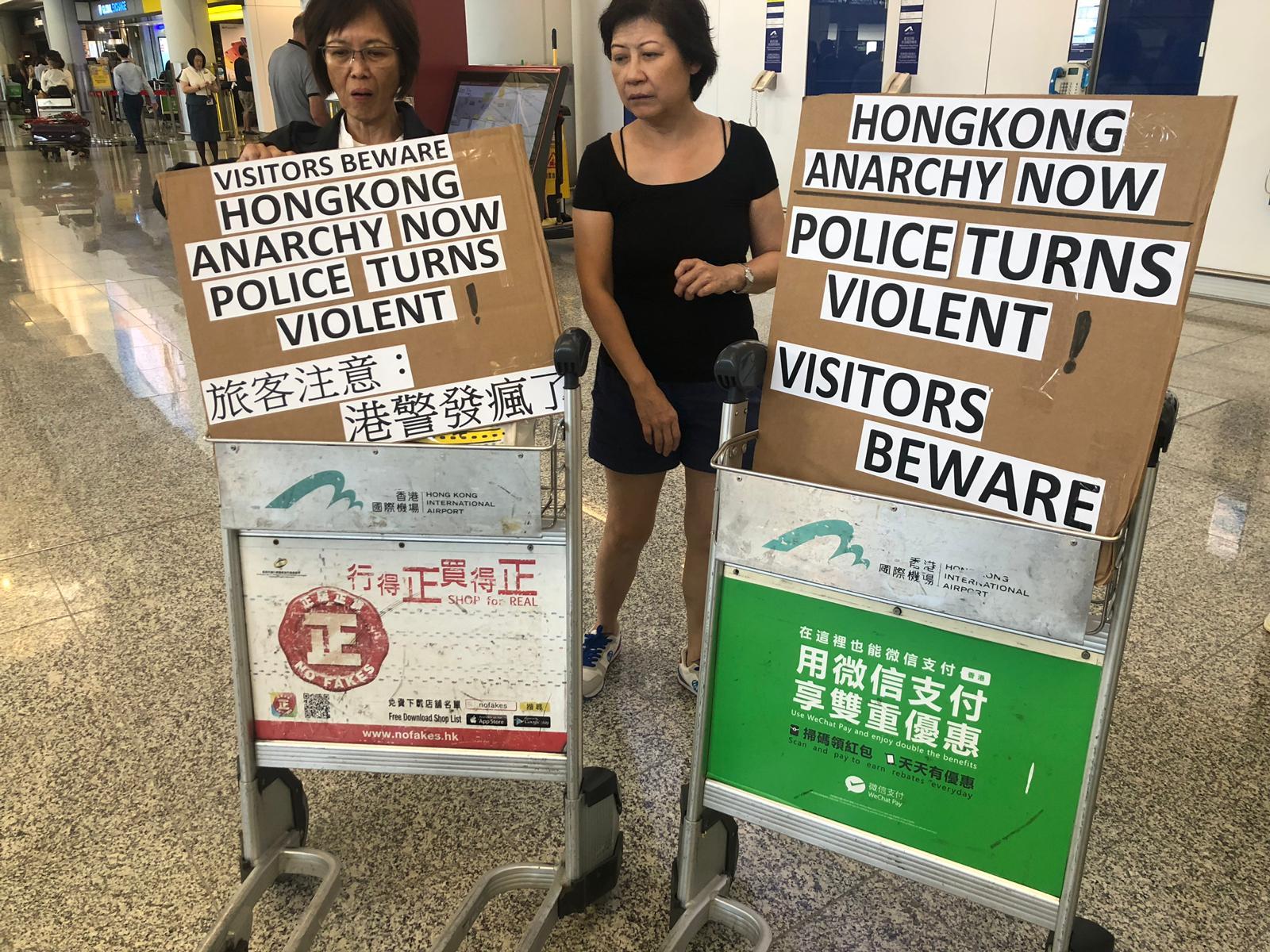 Protesters hoist signs onto luggage carts at Hong Kong's airport.