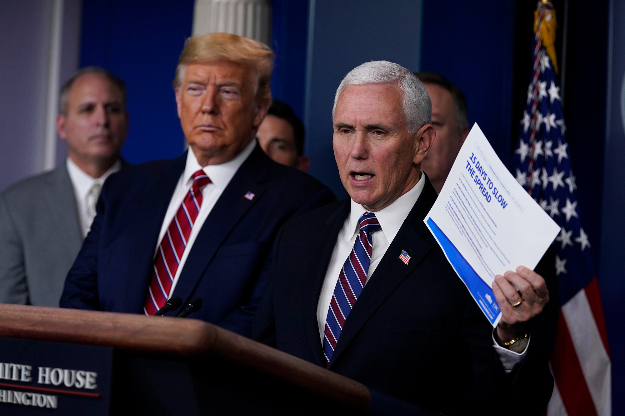 President Donald Trump listens as Vice President Mike Pence speaks during a coronavirus task force briefing at the White House on Friday.