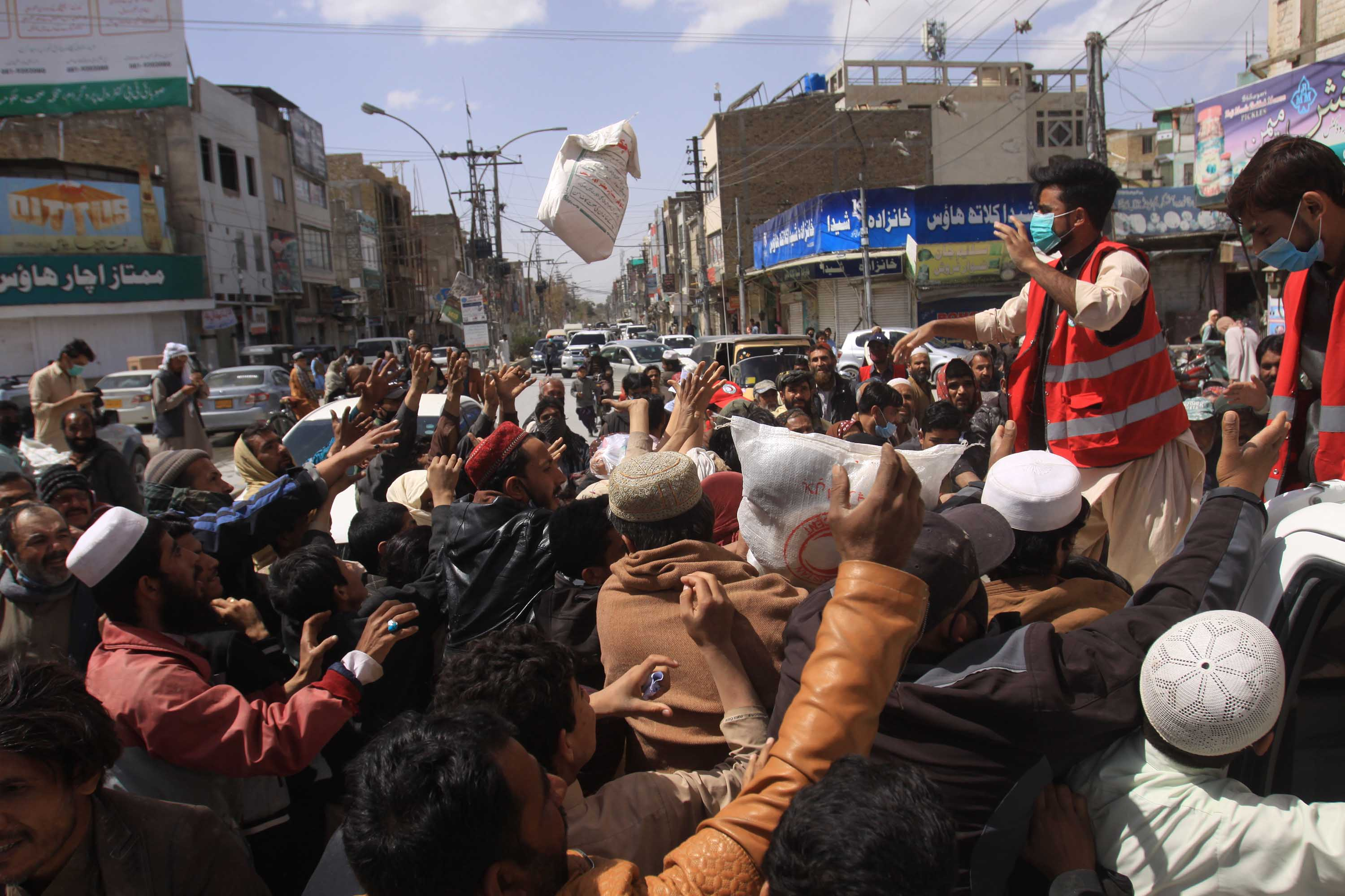Daily wage workers, unemployed due to the coronavirus outbreak, jostle for free food supplies being distributed in Quetta, Pakistan, on Tuesday.