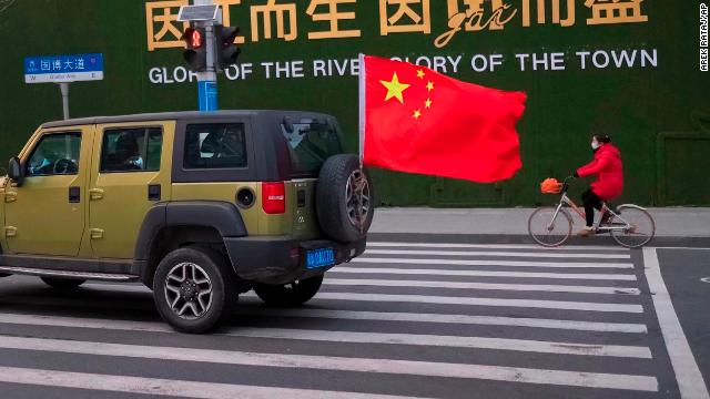 A vehicle flying a Chinese flag drives past a woman wearing a face mask as she rides a bicycle along a street in Wuhan.