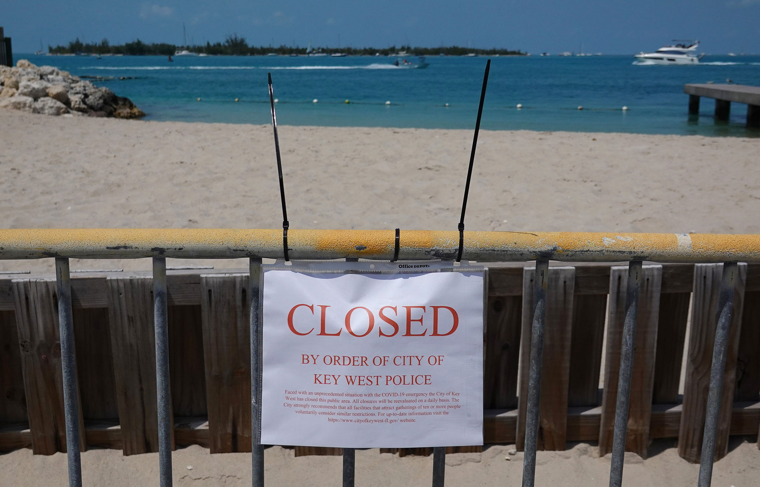 A sign indicates a closed beach in Key West, Florida, in March.