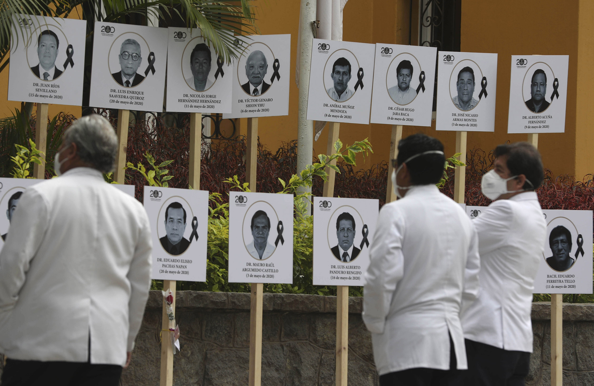 Doctors look at photos of their colleagues who died of COVID-19 after attending patients during the new coronavirus pandemic in Lima, Peru, Friday, on May 29.