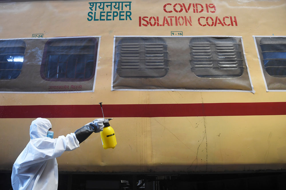 A worker in protective gear sprays disinfectant on a train carriage converted into an isolation ward for Covid-19 patients during a government-imposed nationwide lockdown in Howrah near Kolkata on April 5.