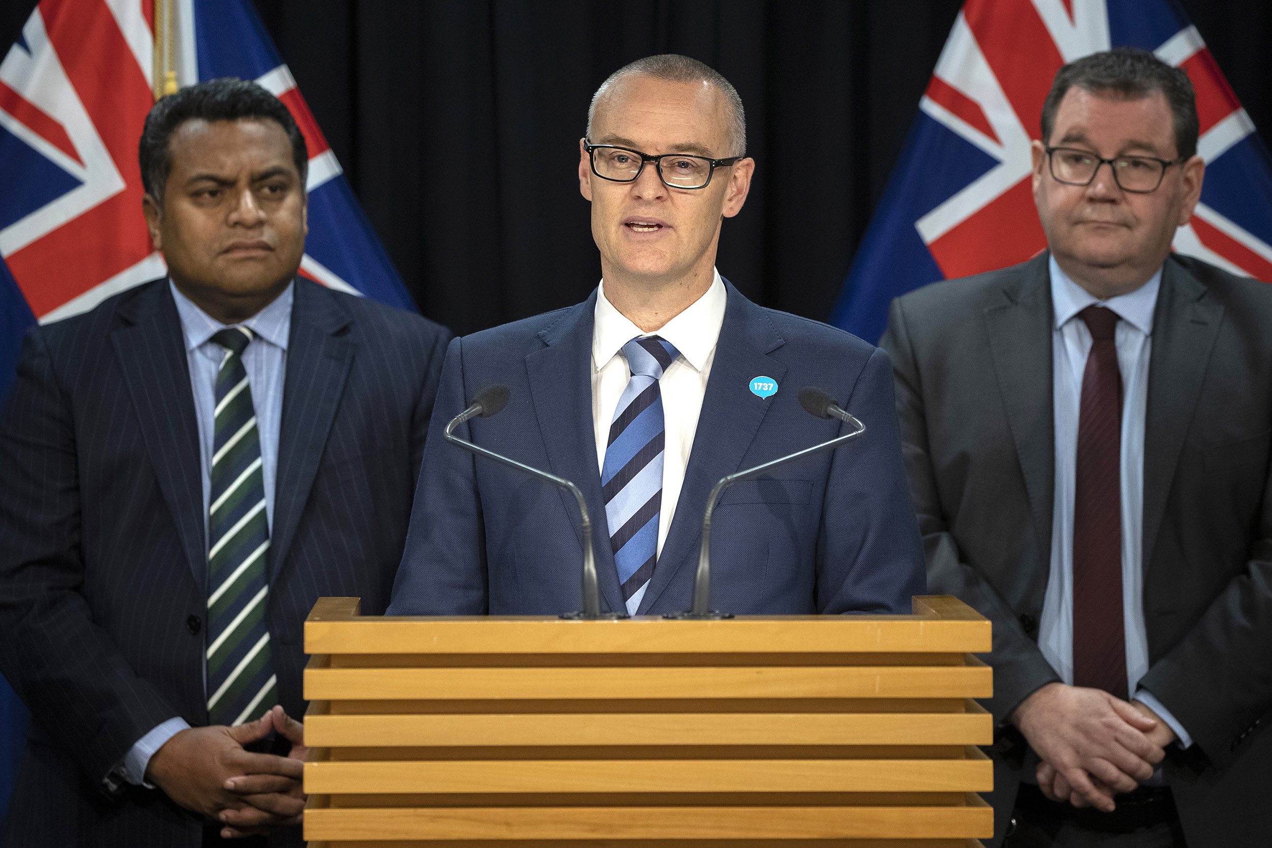 New Zealand Health Minister David Clark, center, announces his resignation during a press conference on July 2.