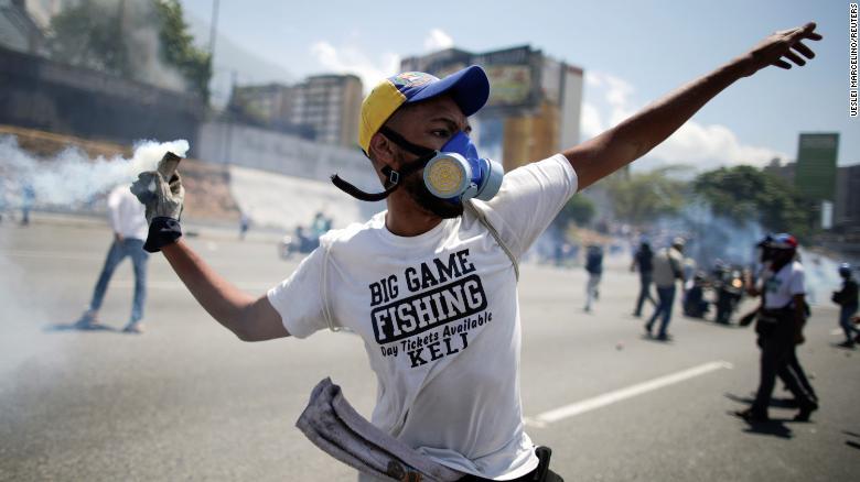 "An opposition demonstrator throws back a tear gas canister on a street near the Generalisimo Francisco de Miranda Airbase ""La Carlota"" in Caracas, Venezuela."