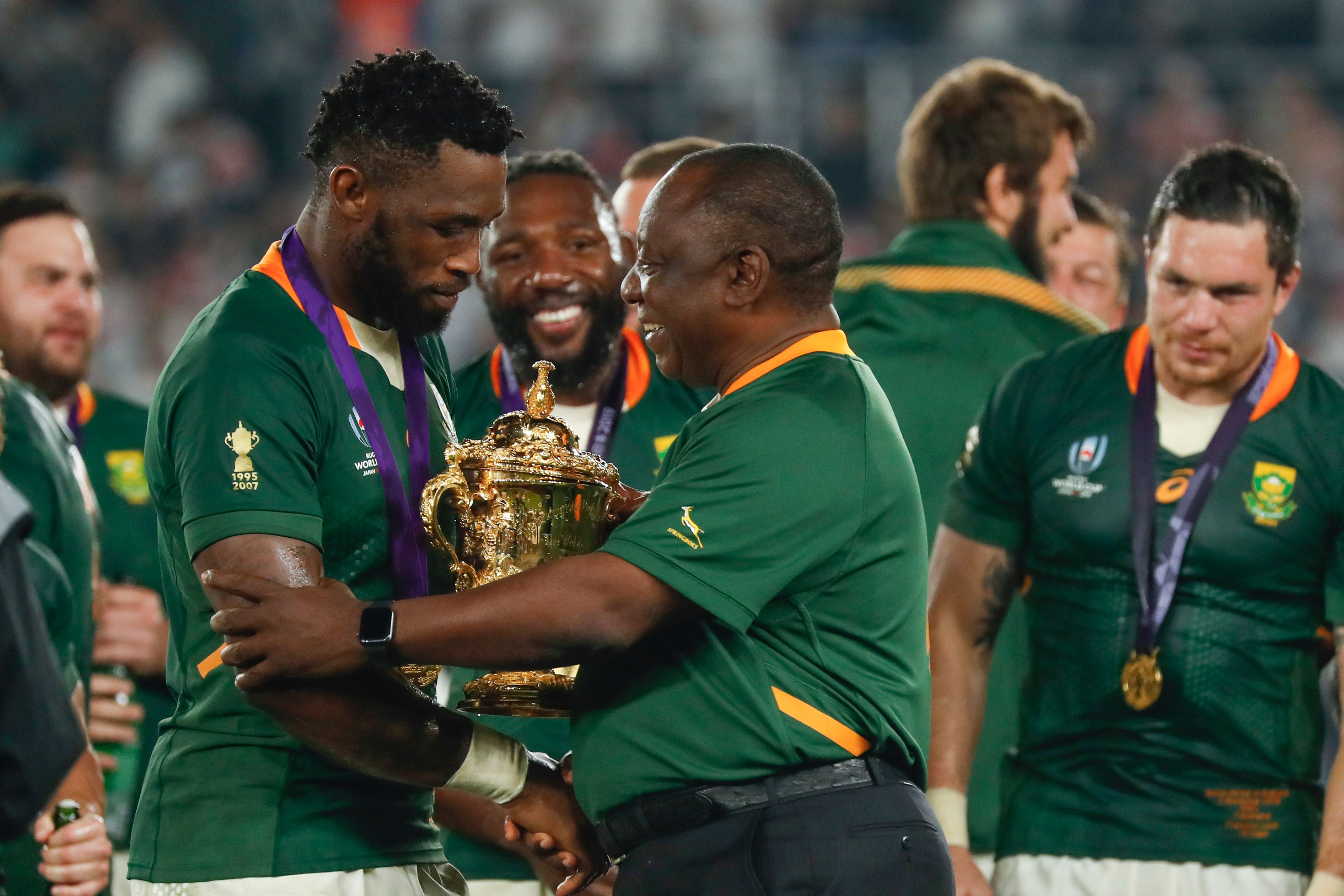 South Africa's President Cyril Ramaphosa (C) congratulates South Africa's flanker Siya Kolisi (L) as they celebrate winning the 2019 Rugby World Cup final.