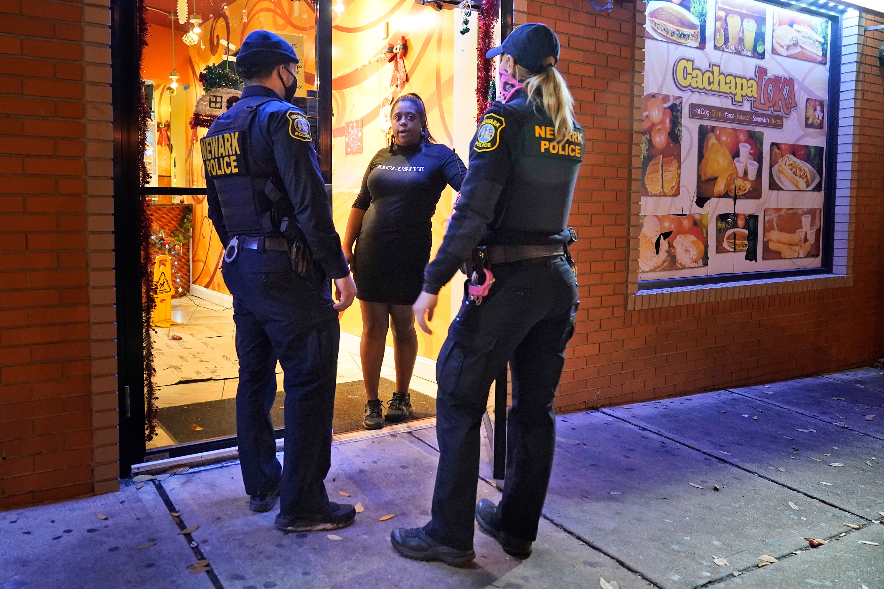 Police officers remind a woman on November 12 in the doorway of a Newark, New Jersey, restaurant of the new curfew and dining regulations in an area where coronavirus cases have recently spiked.