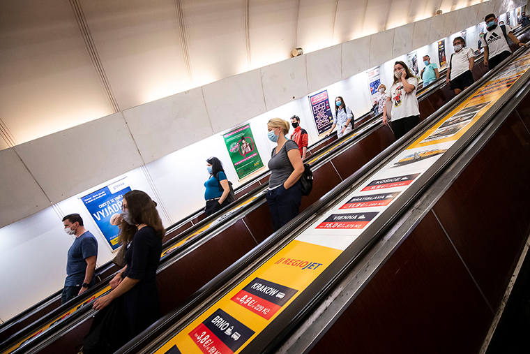 People wearing face masks stand on an escalator in a subway station on September 16, 2020, in Prague, Czech Republic.