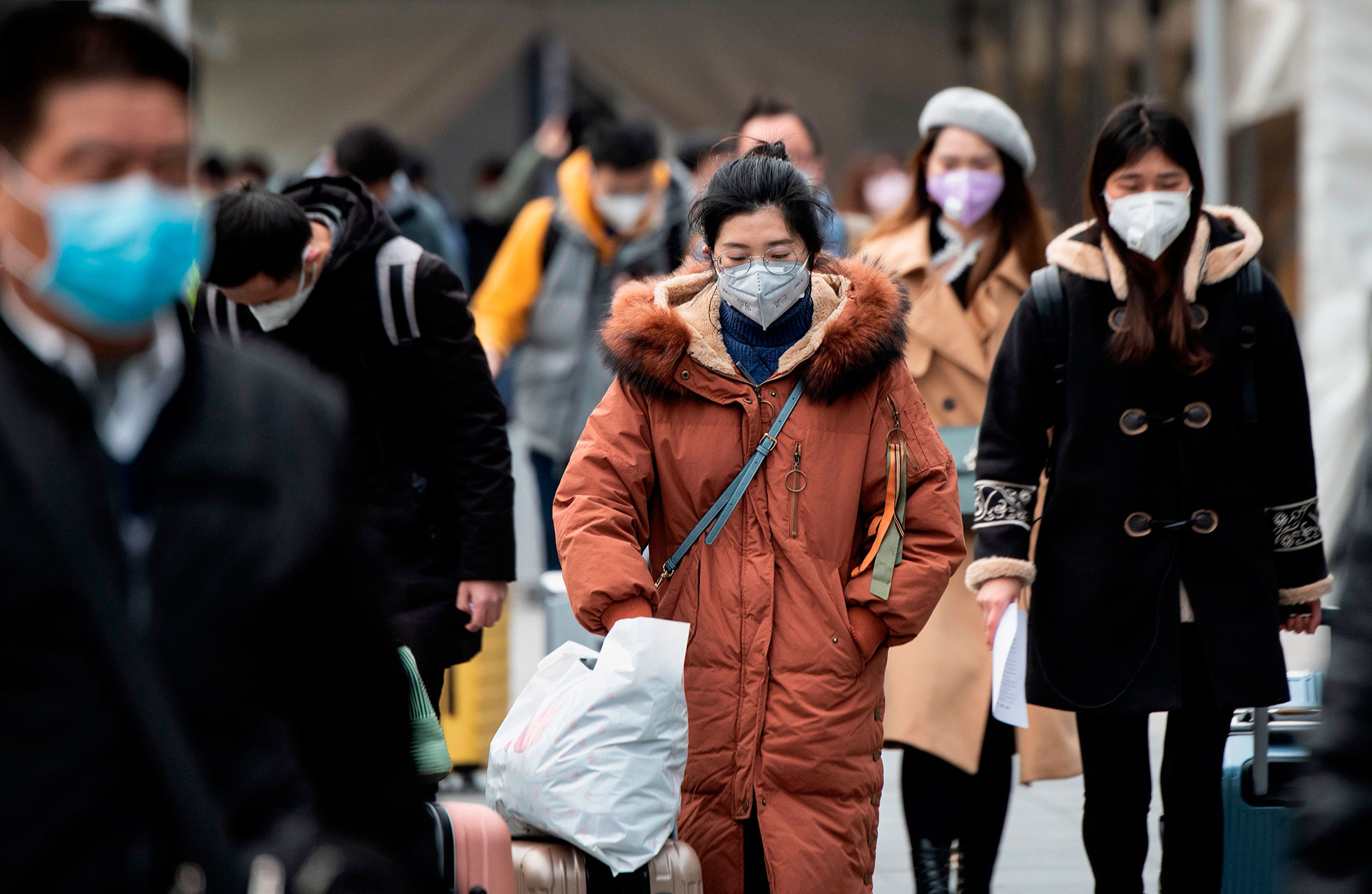 People wear protective face masks as they enter a railway station in Shanghai on Monday.