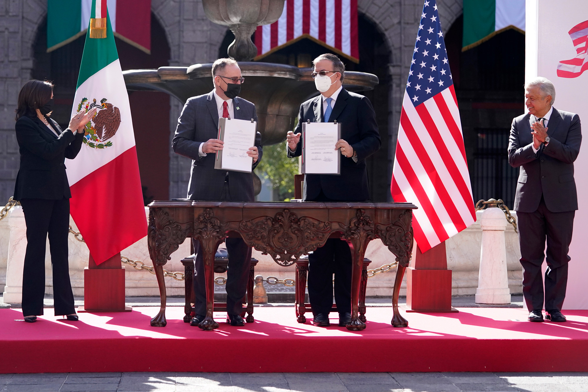 Vice President Kamala Harris, left, and Mexican President Andres Manuel Lopez Obrador, right, applaud a signing on June 8, at the National Palace in Mexico City. The signatories are Mexico's Foreign Minister Marcelo Ebrard Casaubon and John Creamer, Chargé d'Affaires US Embassy.